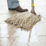 person mopping tile floor