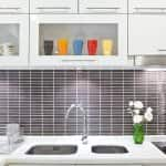 under cabinet lighting in white kitchen with gray subway tile backsplash
