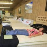 two people shopping for a mattress with a salesman