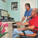 Savvy Enterprizes owner Bryan Swingler, who primarily works with senior citizens, helps client George McMillan learn to use his computer. (Photo by John Zambito)