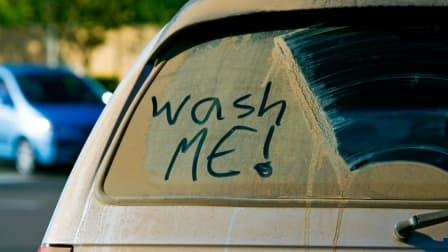 dirty car with 'wash me' on window
