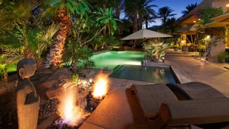 Pool with fire featues, seating, palm trees at night