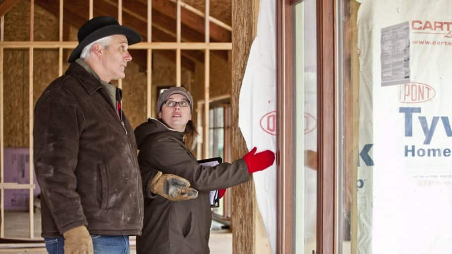 A male homeowner and female LEED verifier look at the inside of a home under construction
