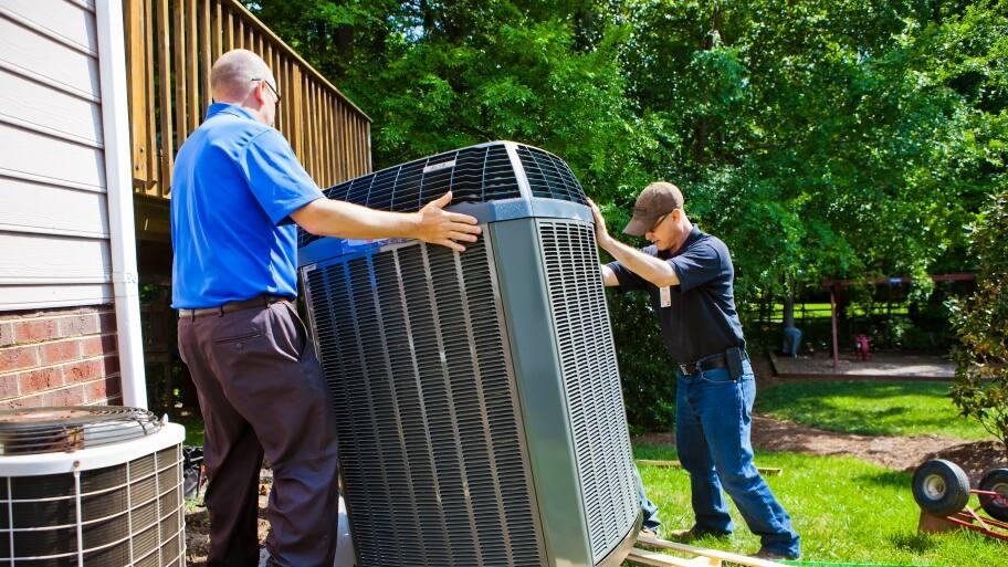 two men installing an HVAC unit