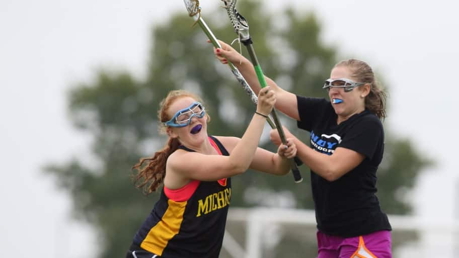 two girls playing lacrosse wearing mouthguards
