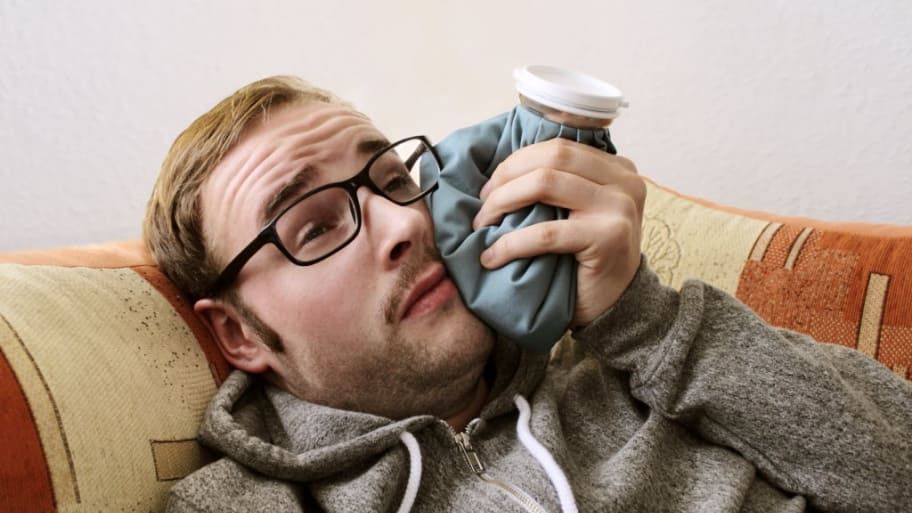 man holds ice pack on his cheek.