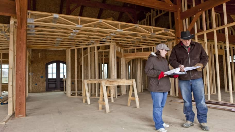 homeowner meets with homebuilder at house under construction