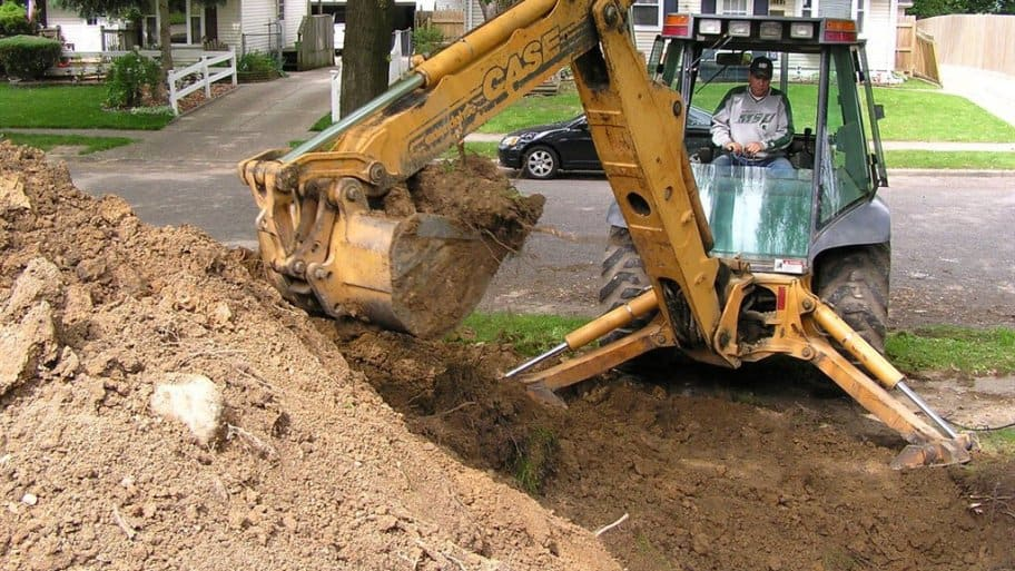 Backhoe excavating ground to dig up and replace damaged sewer pipe.