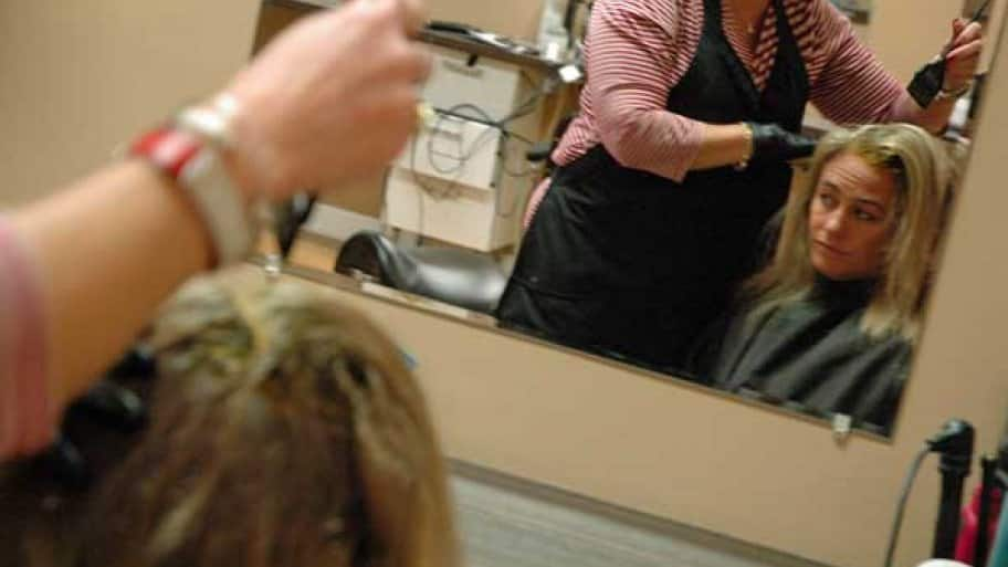 a hair stylist applies color dye to a woman's hair.