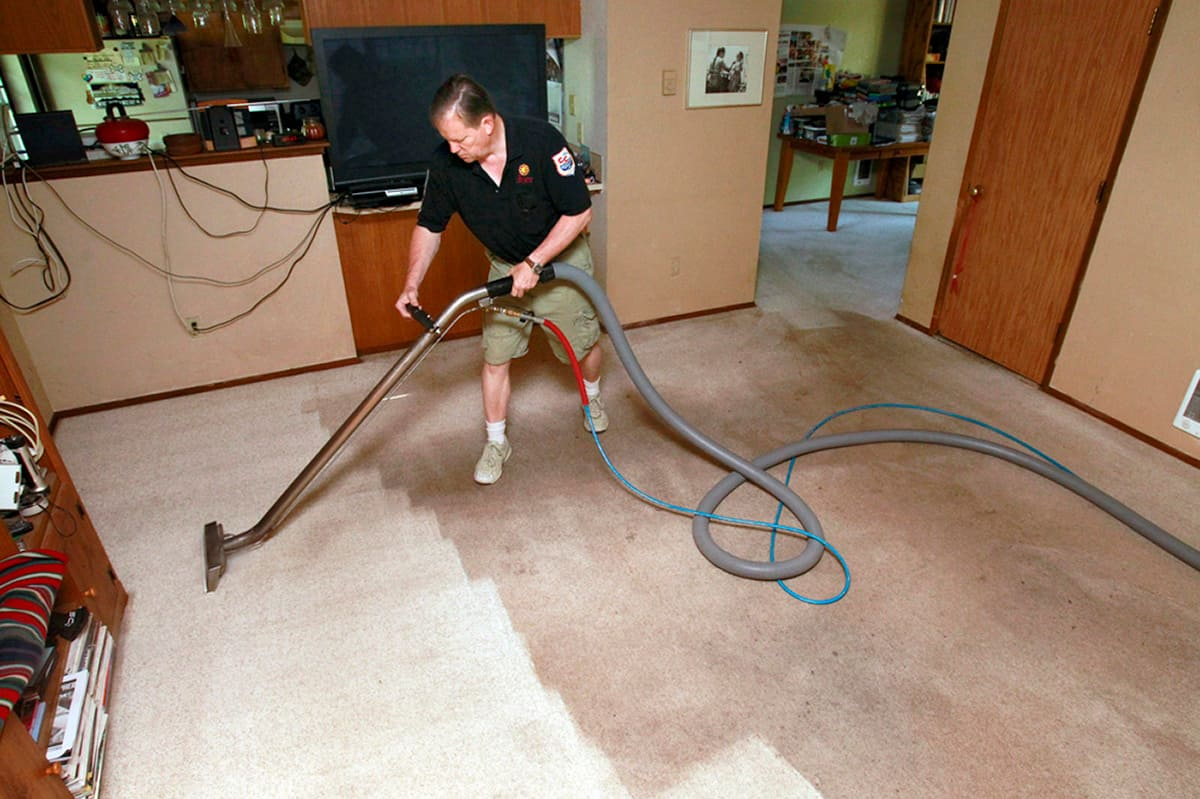 Easy tips for cleaner floors all year long angies list man cleaning beige carpet photo by photo courtesy of dryex baanklon Images