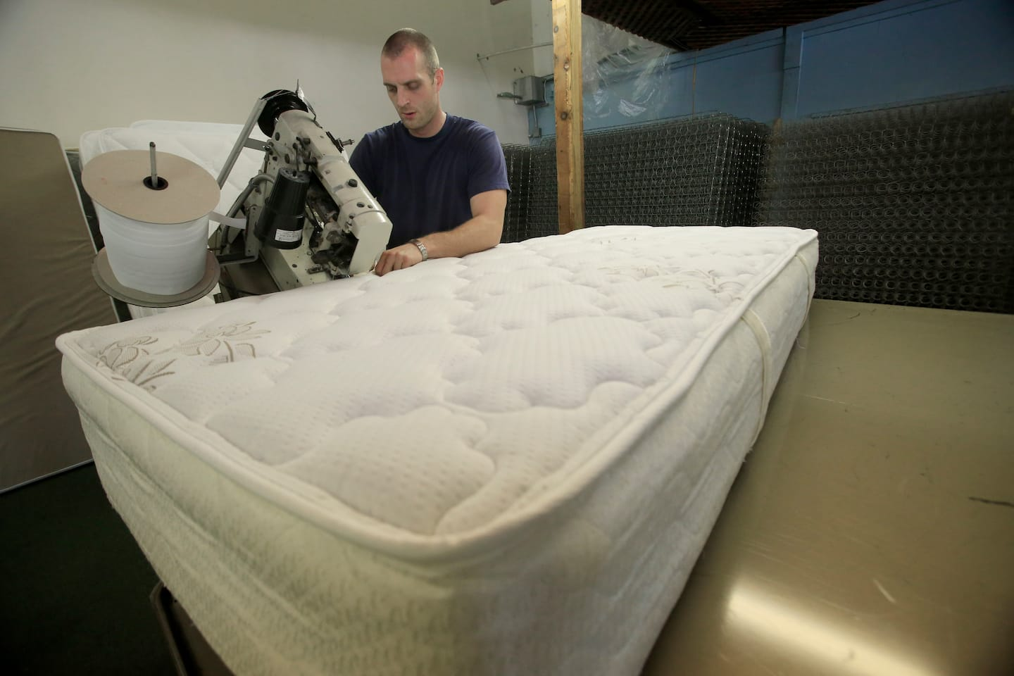 technician sewing mattress together