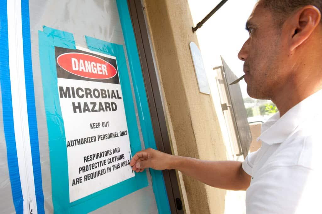 home health hazard inspector hanging a warning sign on a door