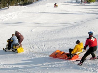 people on skis, sleds on snowy hill