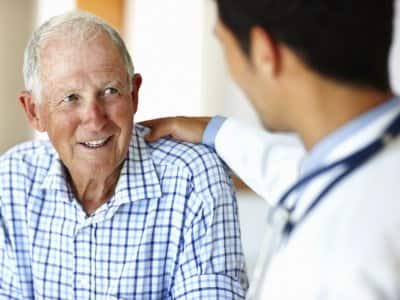 elderly man smiling while talking to a physician