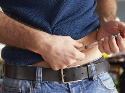 Man giving himself an insulin injection in abdomen