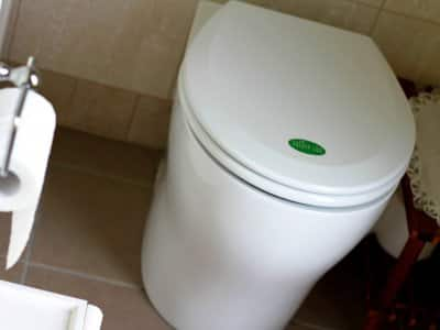 Nature Loo composting toilet in a contemporary bathroom with tile floor and walls