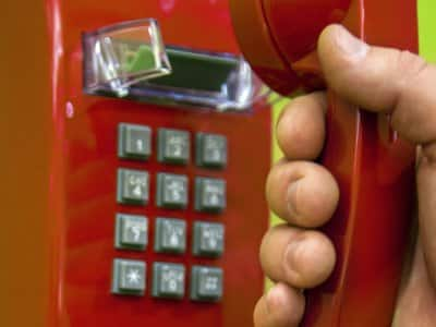 Red old landline telephone with hand grabbing phone on green wall