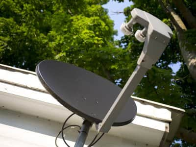 Television cable dish installed on home with service cables