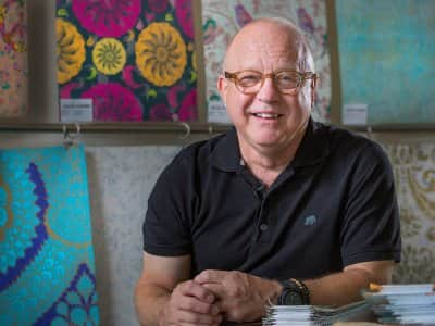 Artist Walter Knabe at his Indianapolis studio with custom wallpaper designs behind him
