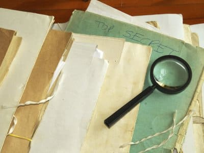 a magnifying glass on top of some old files and folders
