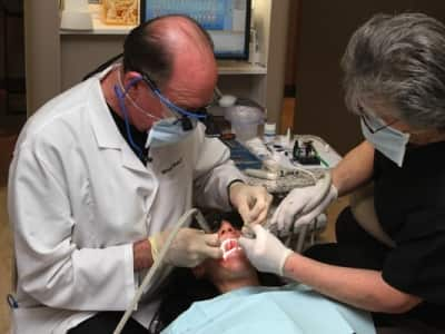 dentist does a dental procedure on a patient.