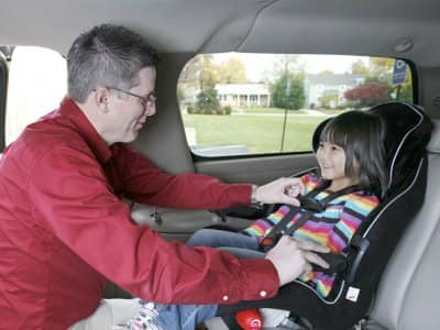father strapping in child to car seat
