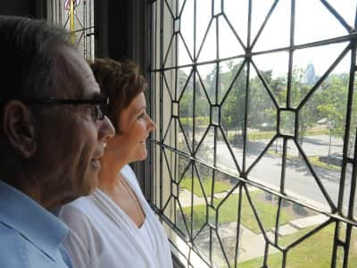 couple stares out apartment window at street