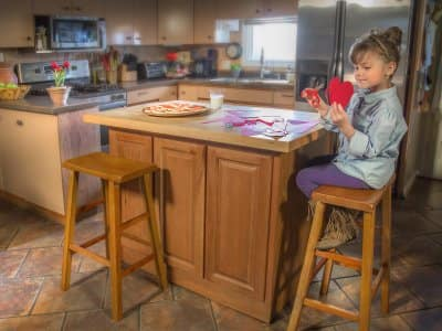 Girl cutting paper heart in kitchen