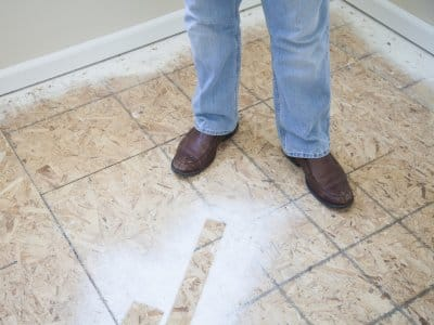 legs and feet of person standing in middle of home improvement work