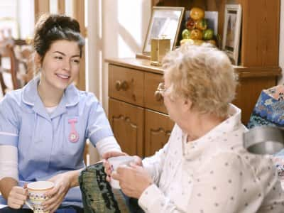A home health care specialist talks with an elderly woman at her home.