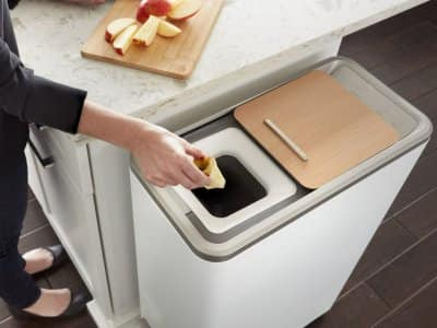 Homeowner dropping apple core into a Zera Food Recycler