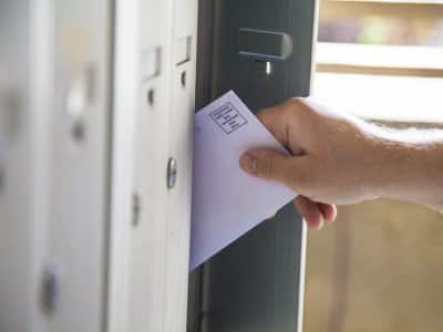 man taking bulk mail from mailbox