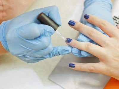 Shellac gel nail polish being applied to woman's hands