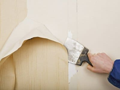 a scraper removing wallpaper