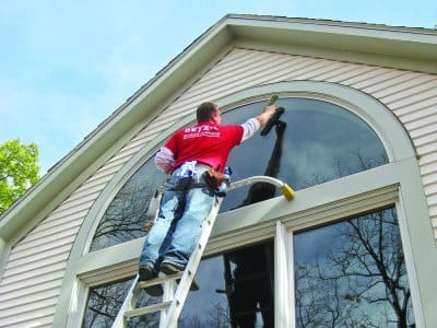 man on ladder washing exterior windows on house
