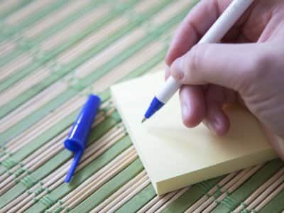 blue pen writing on yellow post it