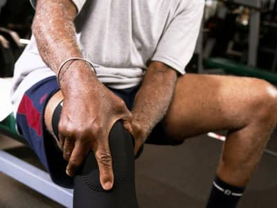 A man sitting in a gym grasps his knee in a knee brace