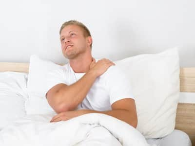 A man in bed, propped up on a pillow, grasps his shoulder in pain