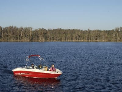 red boat with three people on lake