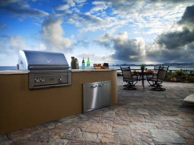 stucco finish open outdoor kitchen on stone patio on near water