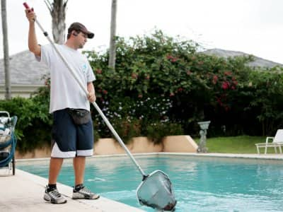 man cleans the surface of a pool with a skimming net.
