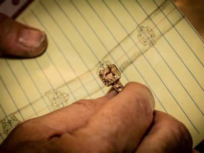Gold ring jewelry in hand over notebook appraisal