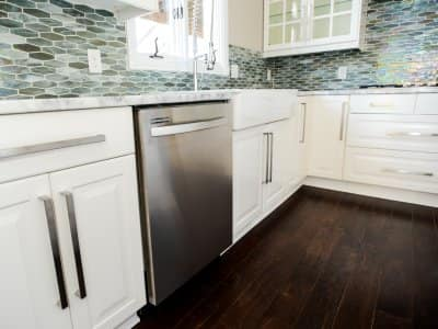 Built-in stainless steel dishwasher, white cabinets, tile backsplash.