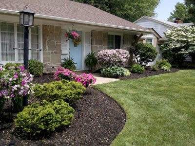 Front-yard landscape with edged flower beds, mulch and post lamp.