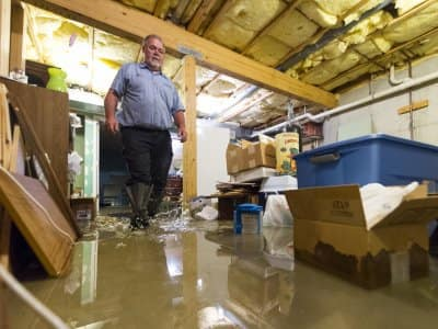 plumber wading through flooded basement