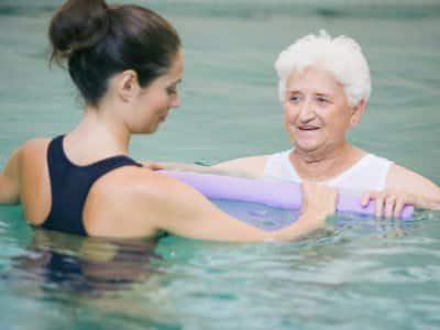 instructor with elderly patient doing water therapy