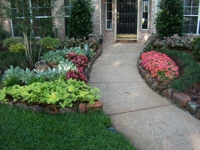 Landscaped entry with flowers, trees, shrubs and brick edging.