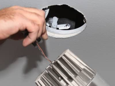 Electrician installs a recessed LED light.
