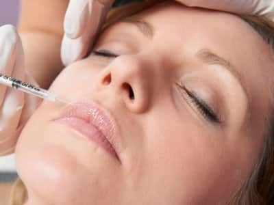 Gloved hands guide a syringe to a woman's lips