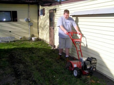 Man pushes a Troy-Bilt Bronco rototiller in the backyard alongside his house.